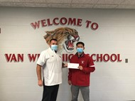 Trent Temple, Van Wert High School Athletic Director, accepts a donation from George Scott, Van Wert Federal Savings Bank Vice President and Senior Lending Officer.