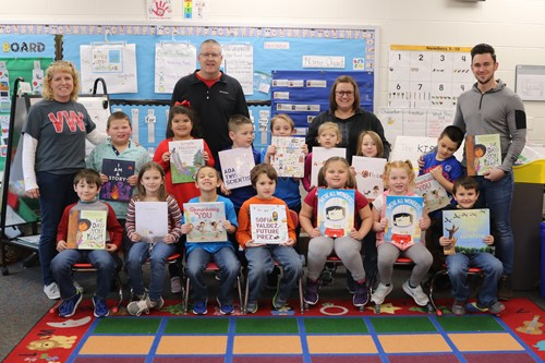Mrs. Foster's class show off several of the books purchased through the recent grant the ECC received