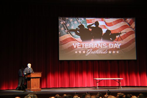 A guest speaker addresses high school students at the 2018 Veteran's Day assembly