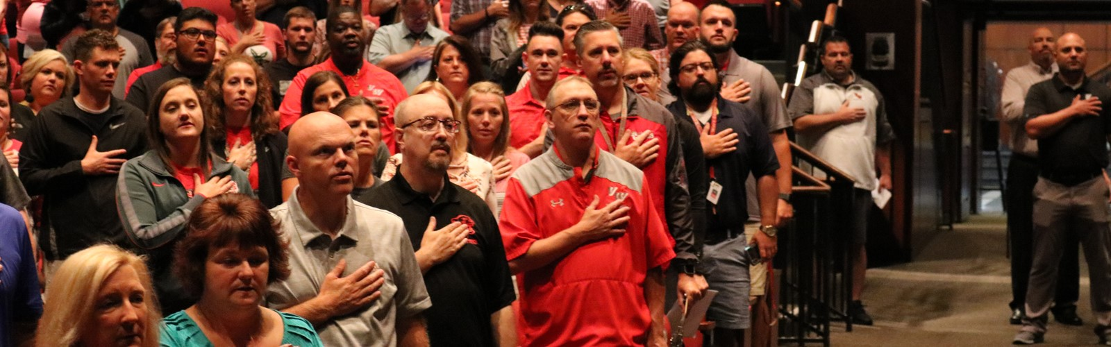 Staff say the Pledge of Allegiance during opening day meetings