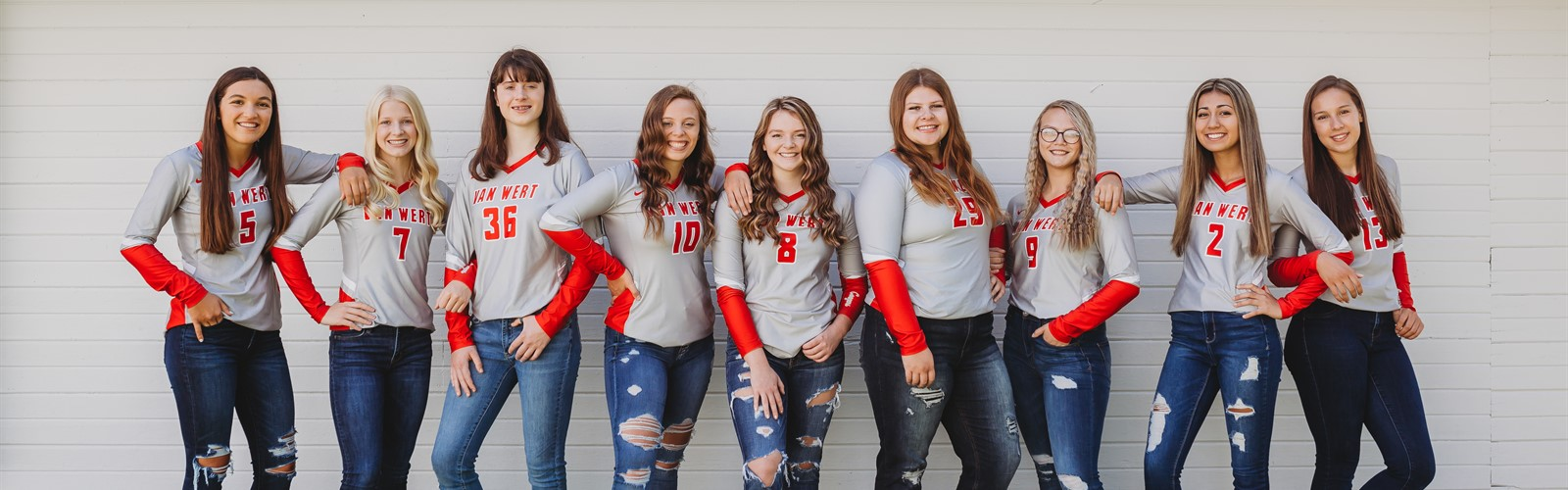 Van Wert volleyball team pose in their jerseys and jeans on front of a white barn