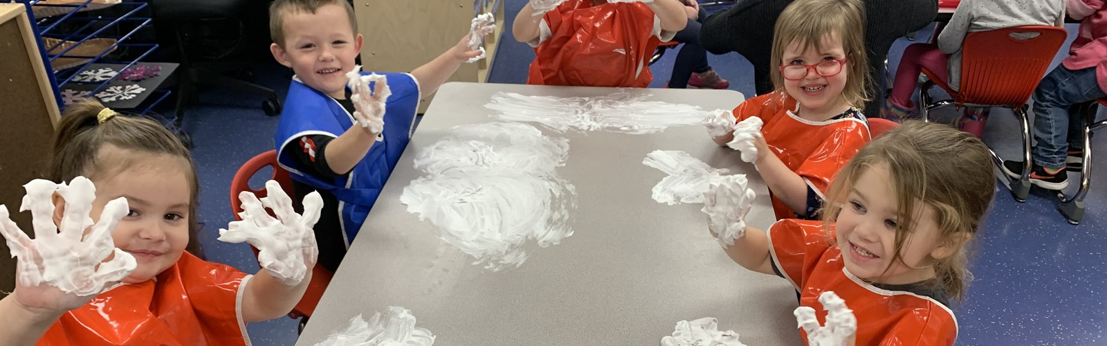 Preschool students hold up their hands with shaving cream on them. They are enjoying and sensory experience and practicing writing letters and drawing shapes.