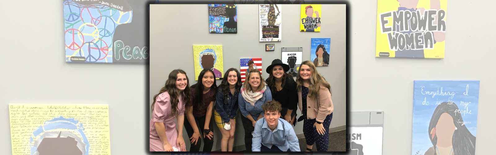 Debbie Jones, Citlali Aguilar-Montiel, Sarah Verville, Mrs. Keber, Ella Hernandez, Emma Wallace and Gage Stemen pose in front of the paintings the students created for the YWCA