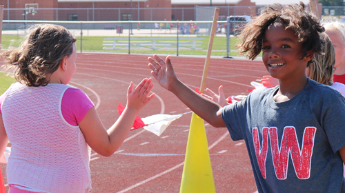 Student high fives a classmate as they finish the one mile fun run