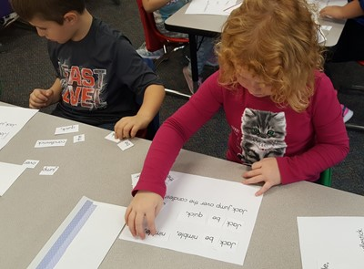 ECC students match words of a familiar poem left to right across the text.